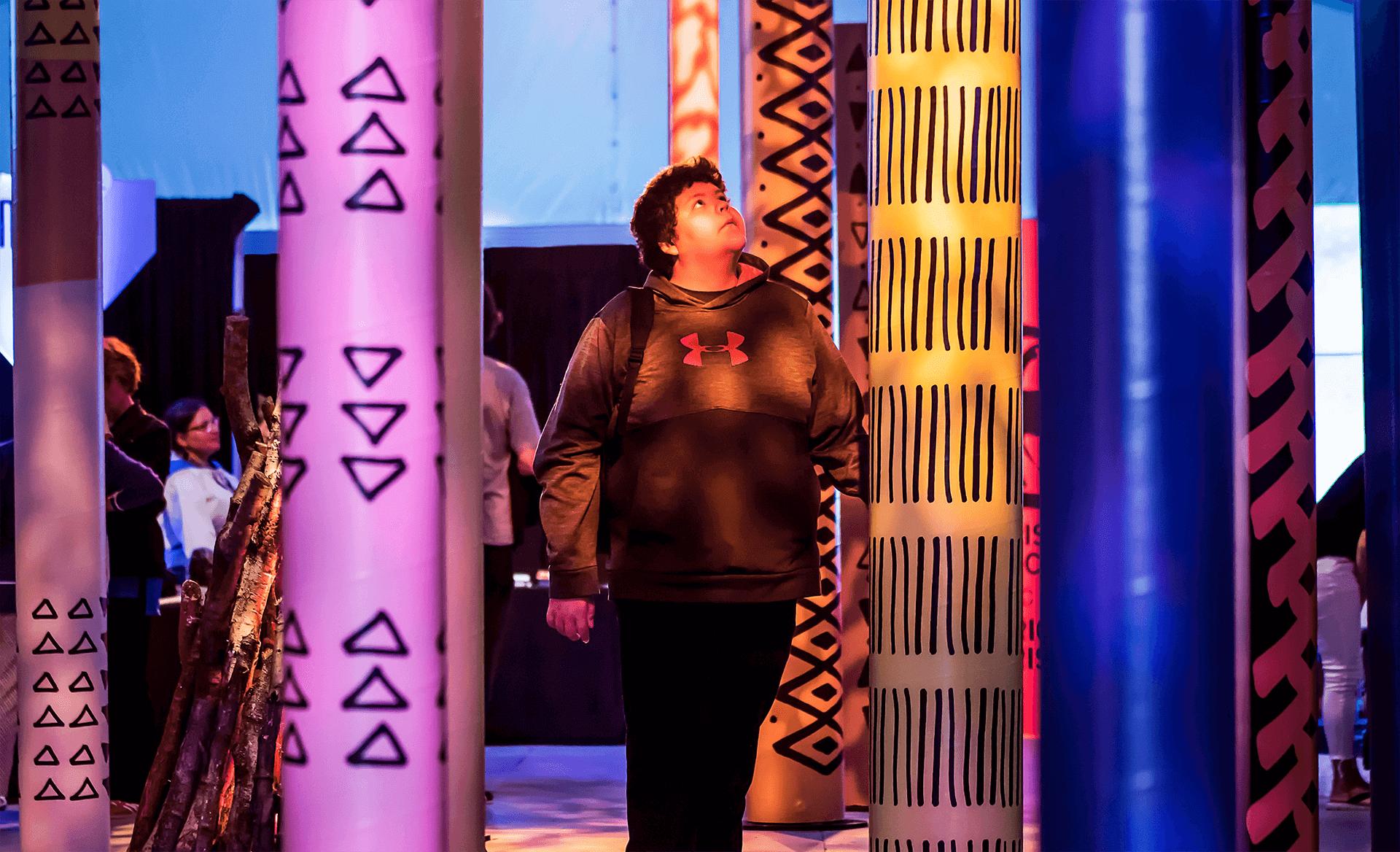 Identité visuelle |Visiteur debout à travers une forêt de poteaux colorés |TAQ