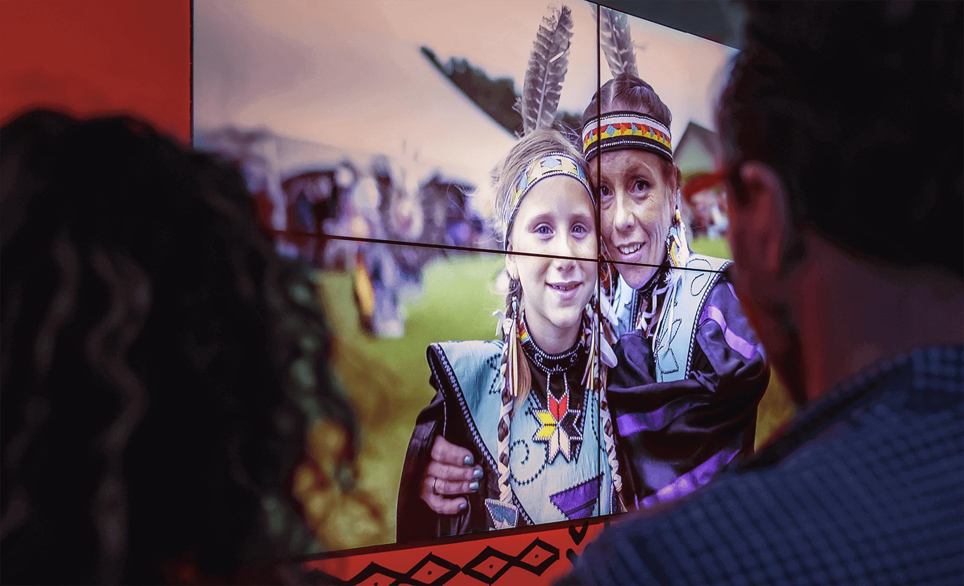 Identité visuelle |Participants en habits traditionnels autochtones sur un écran géant |TAQ